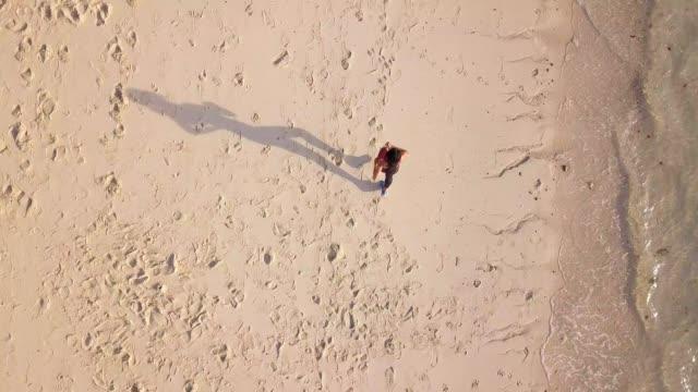 flygfoto spårning skott av sport jogger asiatisk kvinna körs på stranden på ön - pink sunrise bildbanksvideor och videomaterial från bakom kulisserna