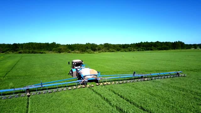 vidéos et rushes de tracteur de vue aérienne saupoudre champ de colza avec des produits chimiques - équipement agricole