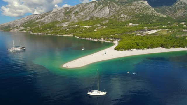 aerial view tranquil scenic view sailboat on sunny blue ocean,bol - zlatni rat,island of brac,croatia - хорватия стоковые видео и кадры b-roll
