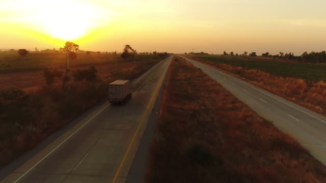 Aerial view truck driving at sunset Aerial view truck driving at sunset horizon over land stock videos & royalty-free footage