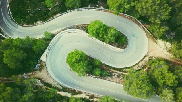 空撮ビデオを 2 つの車線サイクリストと森の中の道を巻線 - 曲線点の映像素材/bロール