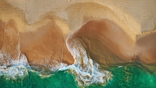 Aerial view waves break on white sand beach at sunset video