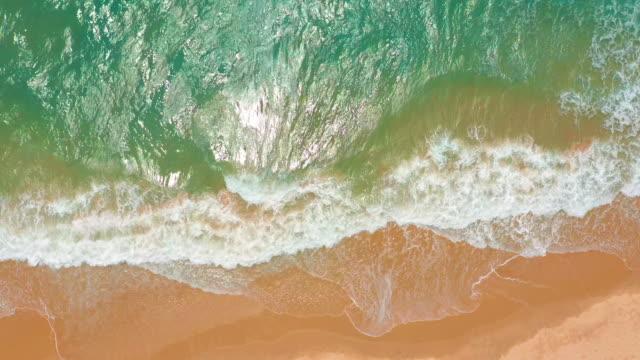 Luchtfoto. golven breken op wit zandstrand. Zee golven op het prachtige strand video