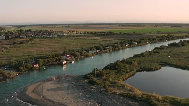 ravenna yakınlarında gün batımında nehrin denize döküldüğü havadan manzara - ravenna stok videoları ve detay görüntü çekimi