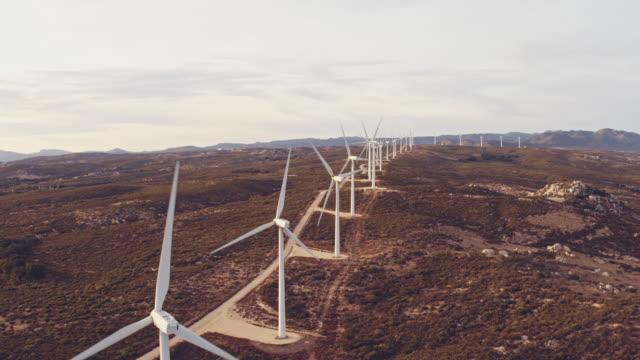 Aerial view wind turbines creating clean renewable energy in mountain landscape at sunset