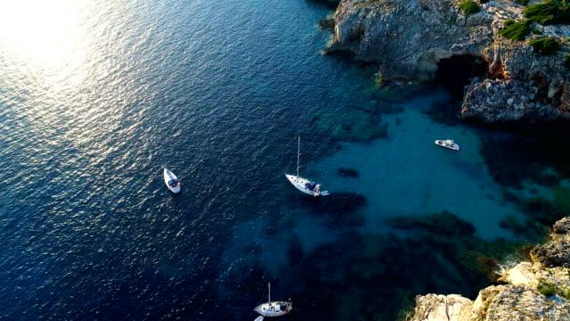 flygvy med en drönare segel båtar i bukten menorca i spanien. underbar utsikt över stranden och medelhavets blåa vatten. på land finns det bara natur med klippor och gräs. - spain solar bildbanksvideor och videomaterial från bakom kulisserna
