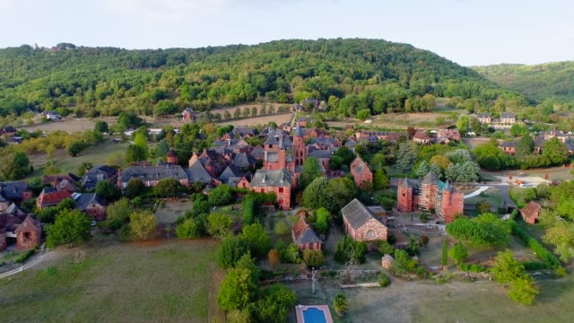 Aerial view with a drone of the village of Collonges-La-Rouge in France. The village is in the middle of a forest and green fields.