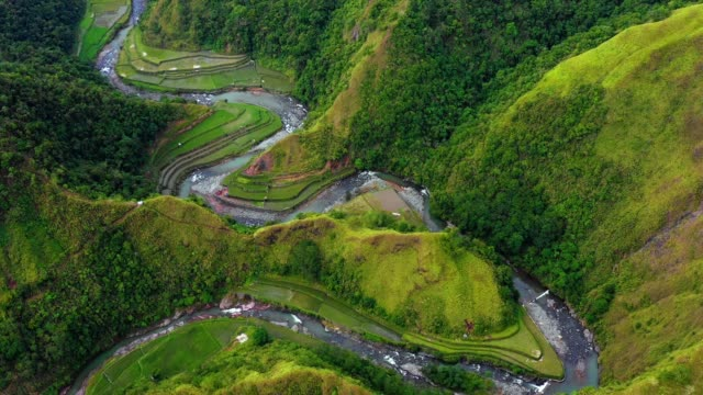 Aerial view with a drone over a stream in the middle of rice terraces in Philippines. Wonderful agriculture in a valley near mountains in a beautiful day - 4K Banaue's rice terraces with a stream or a small river in nature. One of the most beautiful agriculture in Philippines, with the most wonderful view.  Perfect landscape in an amazing place, with the respect of environment banaue stock videos & royalty-free footage