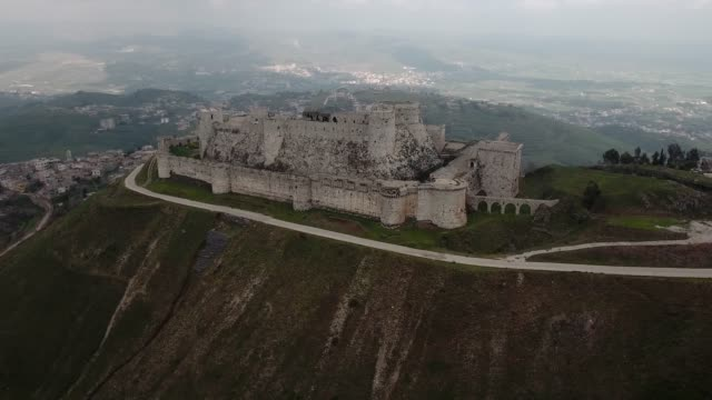 Aerial view with a drone over the Krak des Chevaliers castle in Syria. Wonderful medieval castle on the top of a mountain in ruins after syrian war Aerial view with a drone of Krak des Chevaliers castle in Syria. Wonderful medieval castle on the top of a mountain in ruins after syrian war damascus stock videos & royalty-free footage