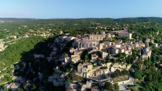 Aerial view wth a drone over the village of Gordes, on the top of a hill in Provence, France. We can see the whole village under the blue sky.