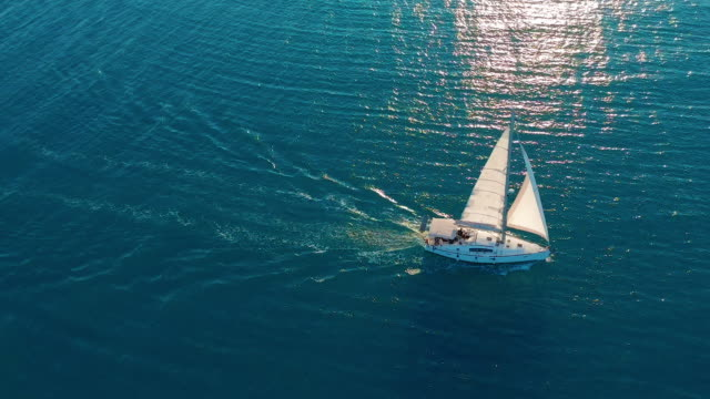 Aerial view. Yacht sailing on open sea at sunny day. Sailing boat in sea Aerial view. Yacht sailing on open sea at sunny day. Sailing boat in sea yachting stock videos & royalty-free footage