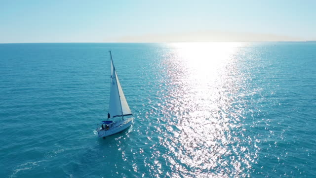 Aerial view. Yacht sailing on opened sea. Sailing boat. Yachting video footage. Yacht from above. Sailboat view from drone