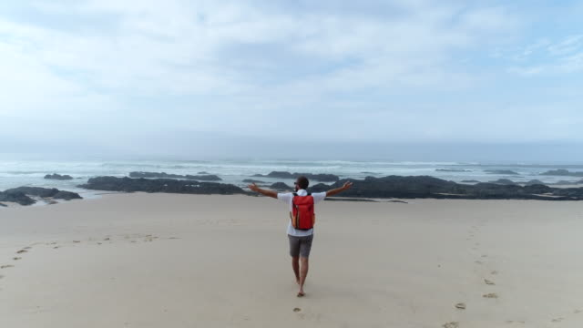 Aerial view- young man walking on beach Young man walking on beach and outstretches arms for freedom and positive emotion. Drone point of view, 4K resolution western cape province stock videos & royalty-free footage
