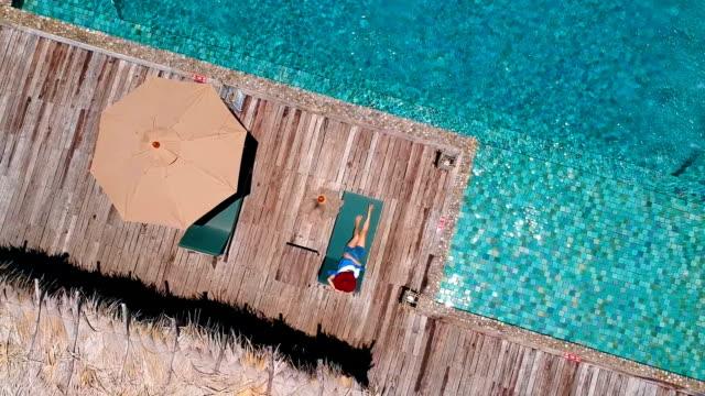 luftbild junge frau beim schwimmen im pool ocean front villa - blickwinkel der aufnahme stock-videos und b-roll-filmmaterial