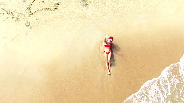 Aerial view. Young woman in santa hat lying on beach. Christmas vacation. 2017 inscription on the sand video