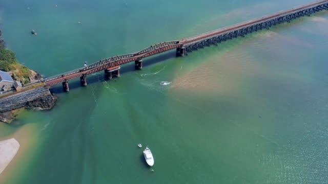 Vue aérienne, zoom à déplacer. Drone sur montante marée actuelle, ancré bateau en mer, le pont de chemin de fer à Barmouth, pays de Galles - Vidéo