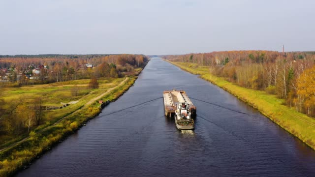 aerial view:barge on the river. autumn landscape, river canal near the forest - речной канал стоковые видео и кадры b-roll