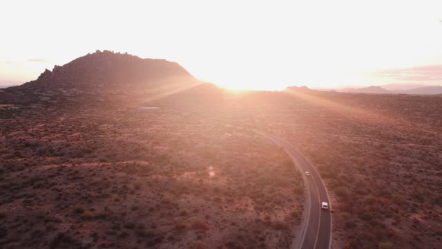 Aerial viewpoint of car driving through the desert mountain valley vista during dramatic sunset with gorgeous sun rays.