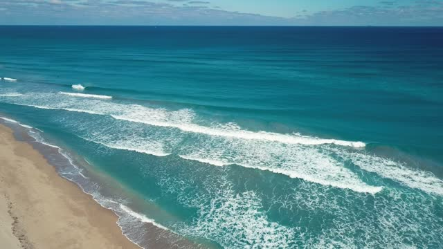 Aerial Views of Teal Ocean Waves Sweeping Across the Palm Beach, Florida Seashore at Mid-Day in January of 2021