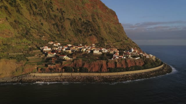 vídeos de stock e filmes b-roll de aerial village in atlantic ocean view at sunset. jardim do mar in madeira island small population. beautiful cinematic little village by the sea with mountains view. - funchal madeira