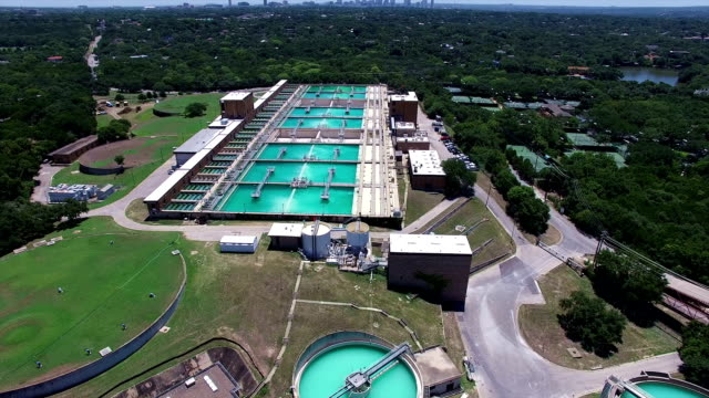 aerial: water treatment purification plant high above the texas hill country next to the colorado river - acquedotto video stock e b–roll