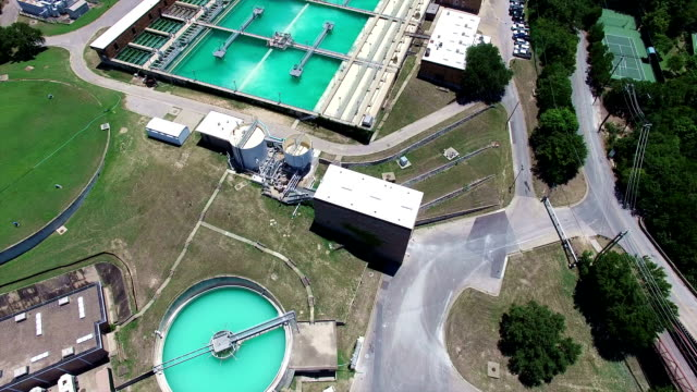 Aerial: Water Treatment Purification Plant long extended version Water Treatment plant purifying water for the citizens in and around the central Texas Austin area. A large water containment unit of large sqaures and another 3 circular shaped cleaning areas. Aerial Drone Footage filmed in 4K . long extended version purified water stock videos & royalty-free footage