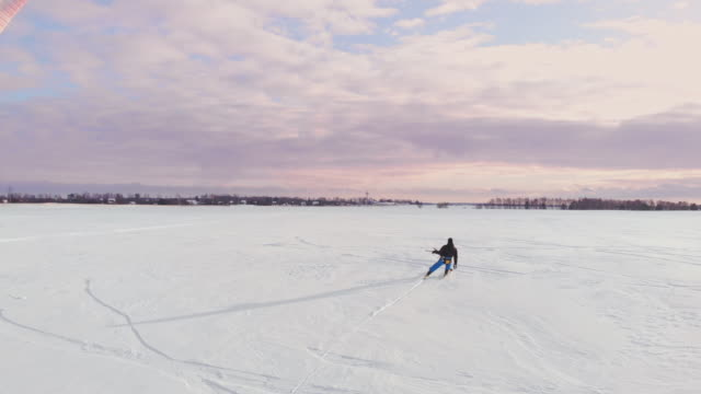 4K aerial winter extreme sport snow kiting competition race with different colorful snow-kites, ski, snowboarders over the ice lake in front of city at blizzard and snow weather from drone