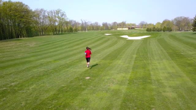 4K. Aerial. Woman runner run on green field. Camera down inclination