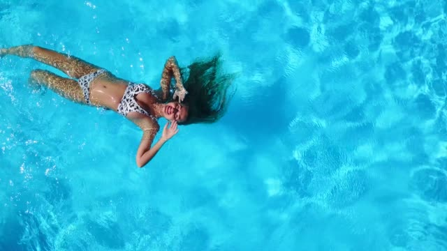 vidéos et rushes de aérienne. femme nageant sur son dos dans la piscine. amis se refroidissant avec l'anneau gonflable, matelas. les jeunes heureux se baignent avec des jouets flottants dans la station de luxe. vue d'en haut. fille dans le bain de soleil de bikini - prendre un bain