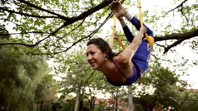 vidéos et rushes de praticien d'yoga aérien s'étend elle-même suspendu sur le hamac. - justaucorps
