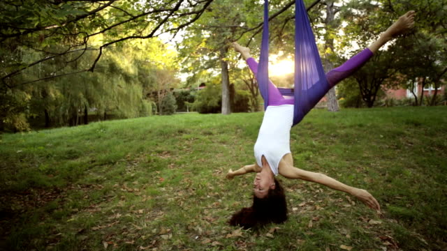 Aerial yoga practitioner stretches herself while suspended on hammock. Aerial yoga practitioner stretches herself while suspended on hammock. Wide shot with headfirst pose nature on background. doing the splits stock videos & royalty-free footage