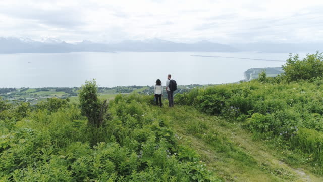 UHD 4K Aerial: Young interracial couple enjoying a beautiful view of Alaska's mountainous coastline after completing a hike