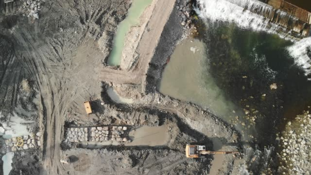 Aerial zoom out of dem construction site Dam construction site in progress, excavator and other construction machinery working on the site. Reconstructing the old and damaged dam. crane construction machinery stock videos & royalty-free footage