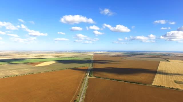 vídeos de stock e filmes b-roll de aerial:country road through fields - linha do horizonte sobre terra