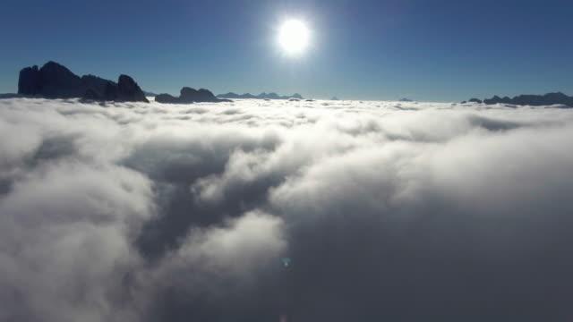 vídeos de stock, filmes e b-roll de antena: voo acima das nuvens em direção ao sol - sol nascente horizonte drone cidade