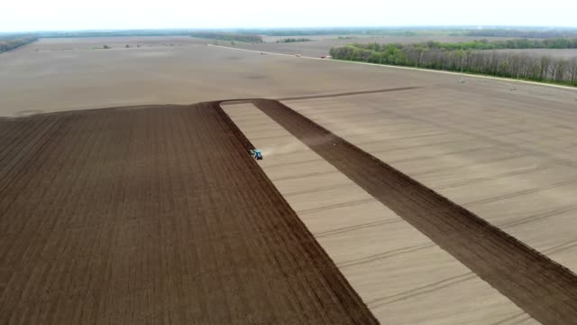 aero. spring sunny day. On an agricultural, farming field, a tractor plows land, soil. Automated planting of potatoes on farms. modern agriculture. Eco farm video