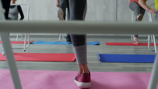 Aerobics for Elderly PAN with low-section of unrecognizable female fitness trainer standing on yoga mat and doing one-leg raises with group of elderly people using folding chairs for support chair stock videos & royalty-free footage