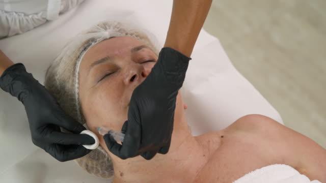 ästhetisches medizinisches verfahren, anti-aging-kosmetologie. spezialist, der mehrere injektionen an ältere patienten. injektionen in kinn- und nackenhaut - kosmetische behandlung stock-videos und b-roll-filmmaterial