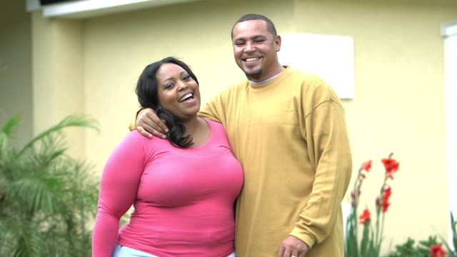 Affectionate black couple standing outside home video