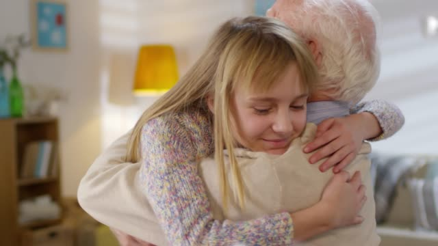 Affectionate Child Hugging Grandfather Medium shot of adorable girl of elementary school age running to her grandfather and embracing him granddaughter stock videos & royalty-free footage