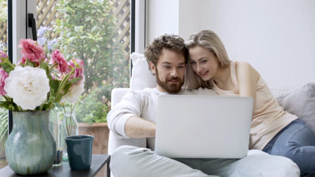 Affectionate couple looking at photos on their laptop Affectionate couple looking at photos on their laptop talking and enjoying the time young couple stock videos & royalty-free footage