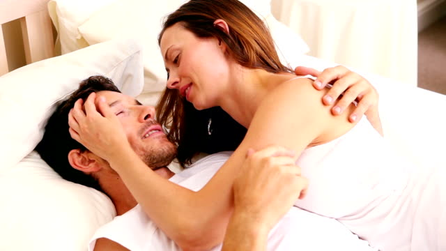 Affectionate couple lying on bed together video