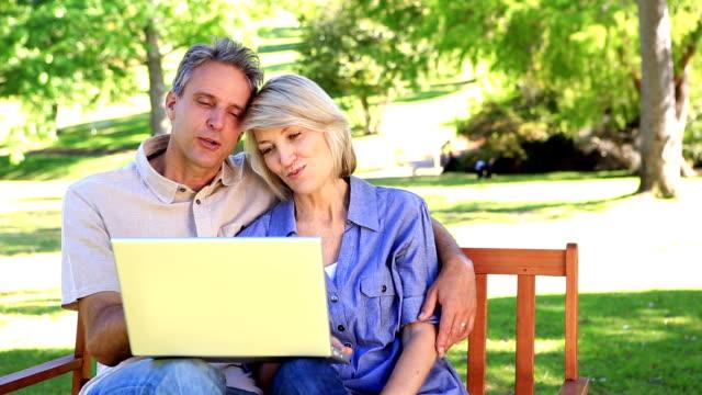 serdeczny para siedzi na ławce w parku przy użyciu laptopa - 50 54 lata filmów i materiałów b-roll