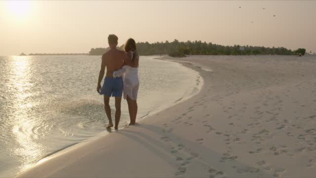 MS Affectionate couple standing at water's edge on tranquil tropical ocean beach at sunset,Maldives