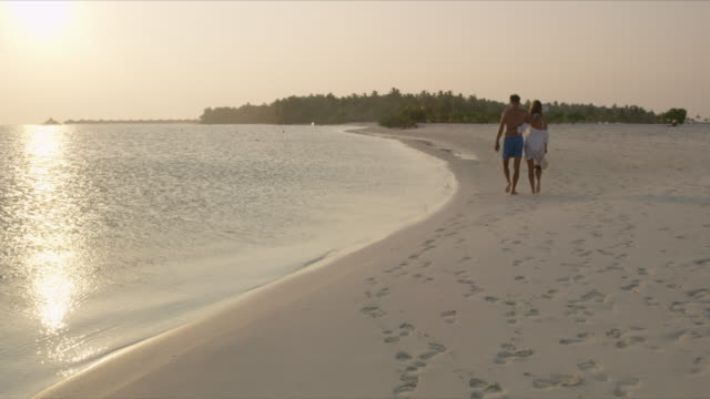 MS Affectionate couple walking on tranquil tropical ocean beach at sunset,Maldives