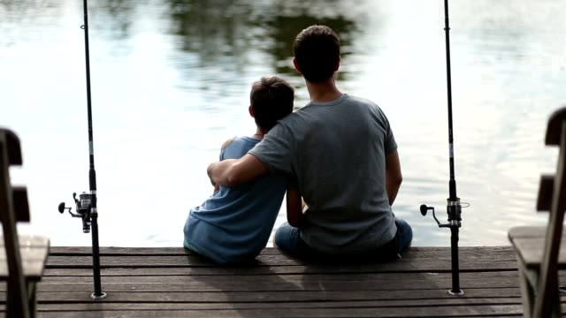 affectionate father embracing son as they fish - fishing video stock e b–roll