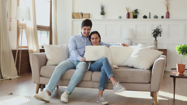 affectionate loving bonding couple relaxing on sofa, using computer. - relazione umana video stock e b–roll