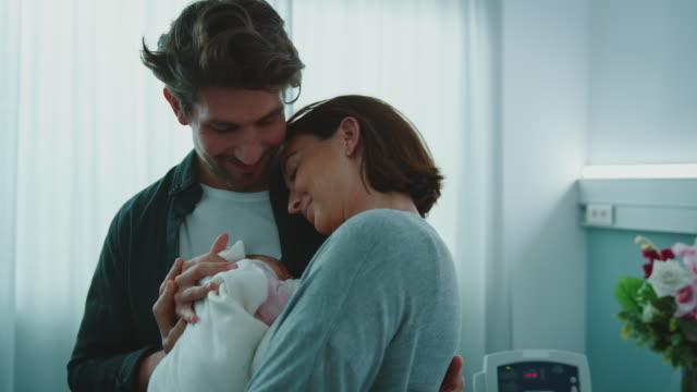 愛情深い男は新生児を抱く女性にキス - 抱きしめる点の映像素材/bロール