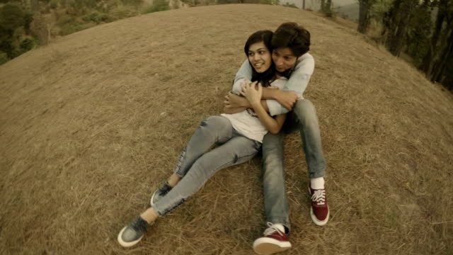 Affectionate multiethnic young couple romancing together in hills. video
