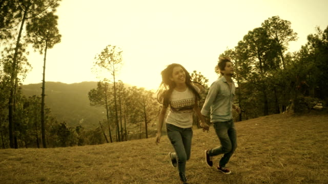 Affectionate multiethnic young couple running together in hills. video